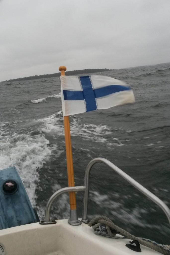 Suomenlippu hulmuten, taustalla Melkki